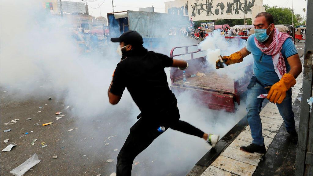 Manifestantes huyen del gas lacrimógeno en la plaza Tahrir durante una de las protestas en Bagdad, Irak.