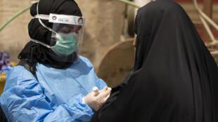 عاملة طبية تجري فحص الكورونا لامرأة في البصرة بجنوب العراق في 2 حزيران/يونيو 2020.
