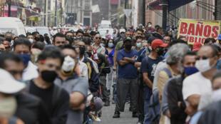 La gente hace cola en una calle esperando pasar por un control peatonal, que limita el acceso en grupos de 20 personas, para ingresar al centro de Ciudad de México, el 6 de julio de 2020