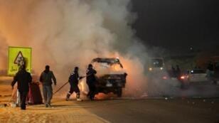 عمال الإطفاء يحاولون إخماد النيران التي اشتعلت في سيارة للشرطة في 8 شباط/فبراير 2015