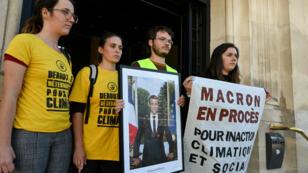 Des militants d'ANV-COP21 avec un portrait décroché d'Emmanuel Macron, le 11 septembre 2019, devant la mairie de Saint-Ouen.