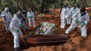 Employees bury the coffin of a person who died from COVID-19 at the Vila Formosa cemetery, in the outskirts of Sao Paulo, Brazil on May 20, 2020