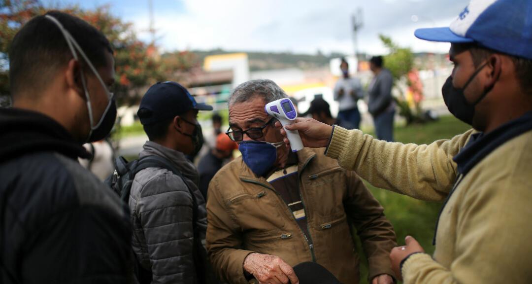 Un hombre se somete a un control de temperatura antes de ingresar a un campamento improvisado de migrantes venezolanos en medio de la pandemia de coronavirus. Bogotá, Colombia, el 8 de junio de 2020.