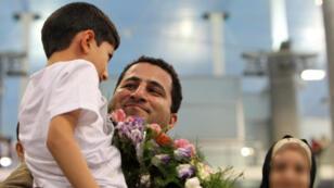 Shahram Amiri prenant son fils dans les bras, à son arrivée à Téhéran en juillet 2010 (archives).