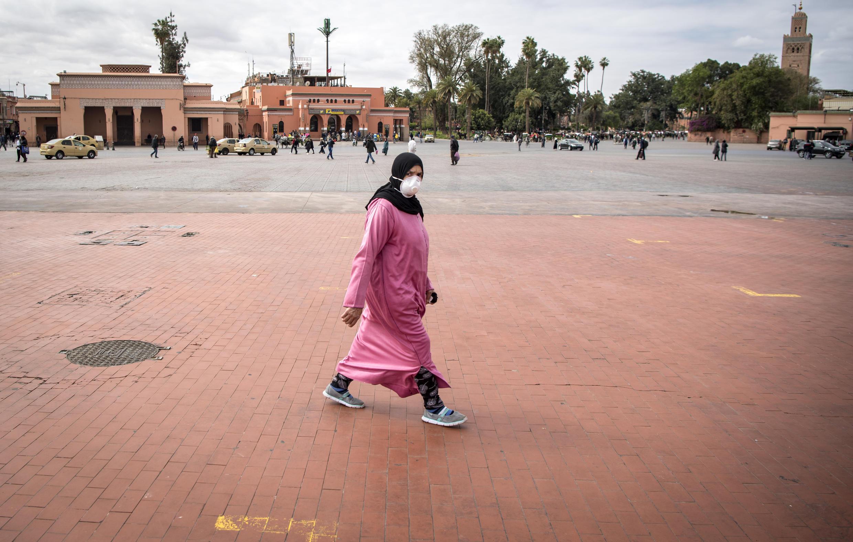 Une femme marocaine portant un masque de protection traverse la place Jemaa el-Fna, presque déserte, dans le centre de Marrakech, le 17 mars 2020.