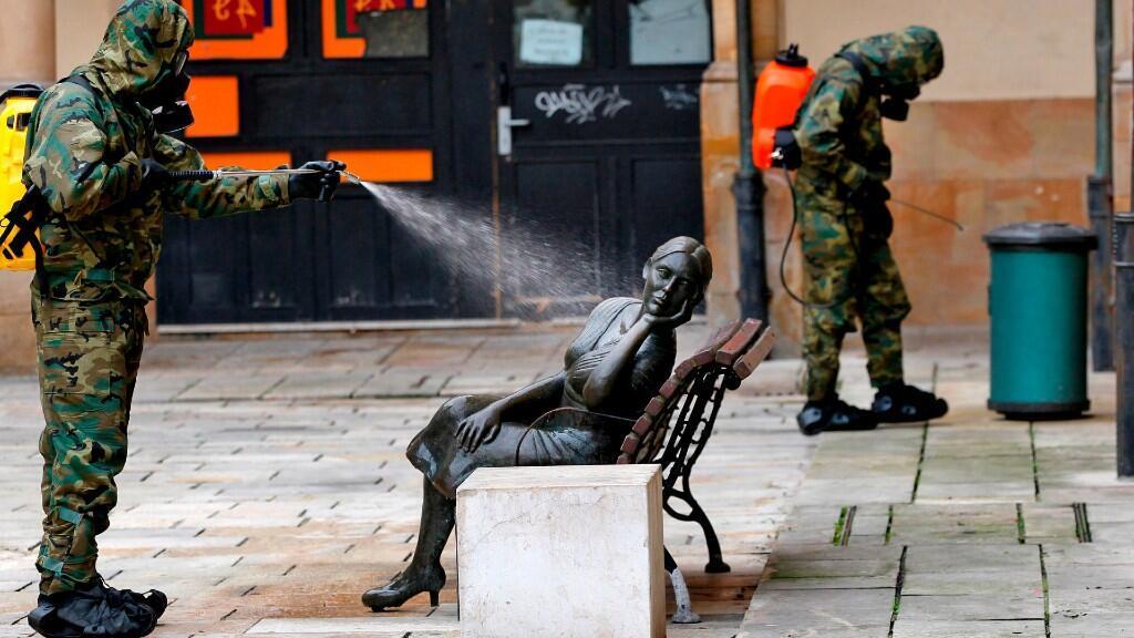 Un soldado desinfecta una escultura en una de las plazas del mercado del Fontán, este domingo, en Oviedo, España. 12 de abril de 2020.