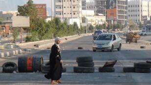 Une femme traverse devant un barrage routier, à Aden, au Yémen.