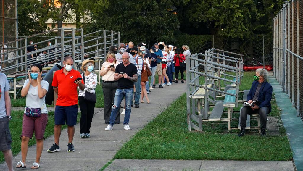 La gente espera en la fila para emitir su voto para las próximas elecciones presidenciales cuando comience la votación anticipada en Houston, Texas, EE. UU., 13 de octubre de 2020.
