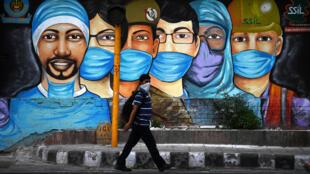 Un homme passe devant une fresque de rue représentant des personnels luttant contre le coronavirus, le 14 juillet 2020 à New Delhi