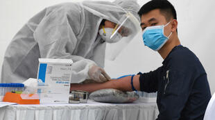 A health worker takes a blood sample from a resident at a makeshift rapid testing centre near Bach Mai hospital in Hanoi on March 31, 2020.