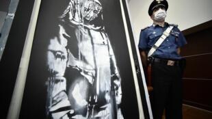 Un policier italien à côté de l'oeuvre de Banksy, volée au Bataclan en 2019, et retrouvée en Italie, lors d'une conférence de presse, le 11 juin 2020 à l'Aquila