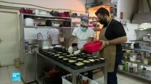 متطوعان في إحدى الجمعيات الإنسانية في لبنان يعملان على تأمين وجبات غذائية لمواطنين محتاجين.