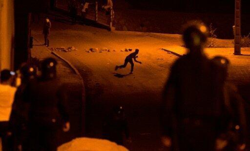 متظاهر يرشق قوات الامن بالحجارة في مدينة امزورن في شمال المغرب مساء 10 حزيران/يونيو 2017