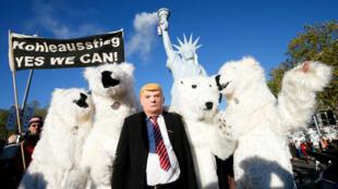 Manifestantes disfrazados posan frente a una réplica de la Estatua de la Libertad que emite humo en Bonn, Alemania. 11/04/2017