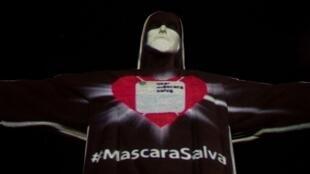 Une projection sur la célèbre statue du Christ rédempteur, sur le Corcovado à Rio de Janeiro, le 3 mai 2020, donne l'impression que le visage de Jésus est recouvert d'un masque de protection, pour encourager la population à en porter.
