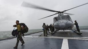 Searchers land on an Indonesian warship