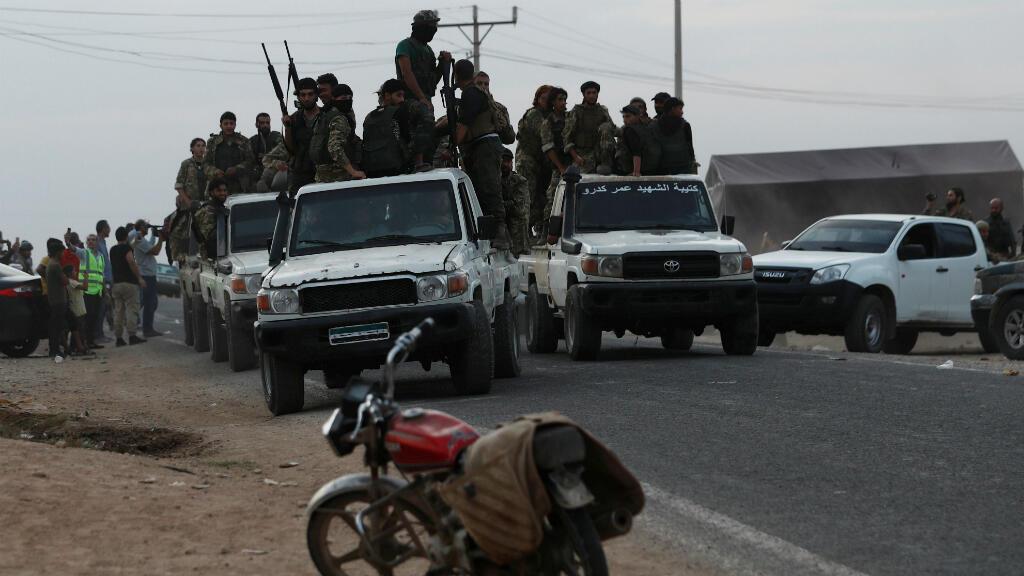 Combatientes rebeldes sirios respaldados por Turquía conducen un camión para cruzar a Siria, cerca de la ciudad fronteriza de Akcakale en la provincia de Sanliurfa, Turquía, el 17 de octubre de 2019.