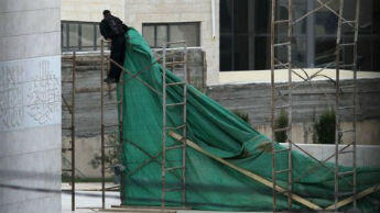 A Palestinian worker places a plastic tarp around the mausoleum of the late Palestinian leader Yasser Arafat, in the West Bank city of Ramallah.