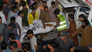 Pakistani volunteers transport the body of a blast victim after a suicide bomb attack near Wagah border on November 2, 2014