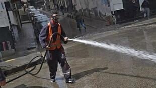 Algiers March 27 Man washing a street AFP