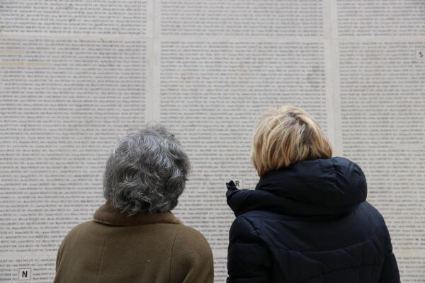 Nicole Minot et Claire Pikovsky devant le mur où sont inscrits les noms des déportés au Mémorial de la Shoah, dont ceux de la famille de Louise Pikovsky.