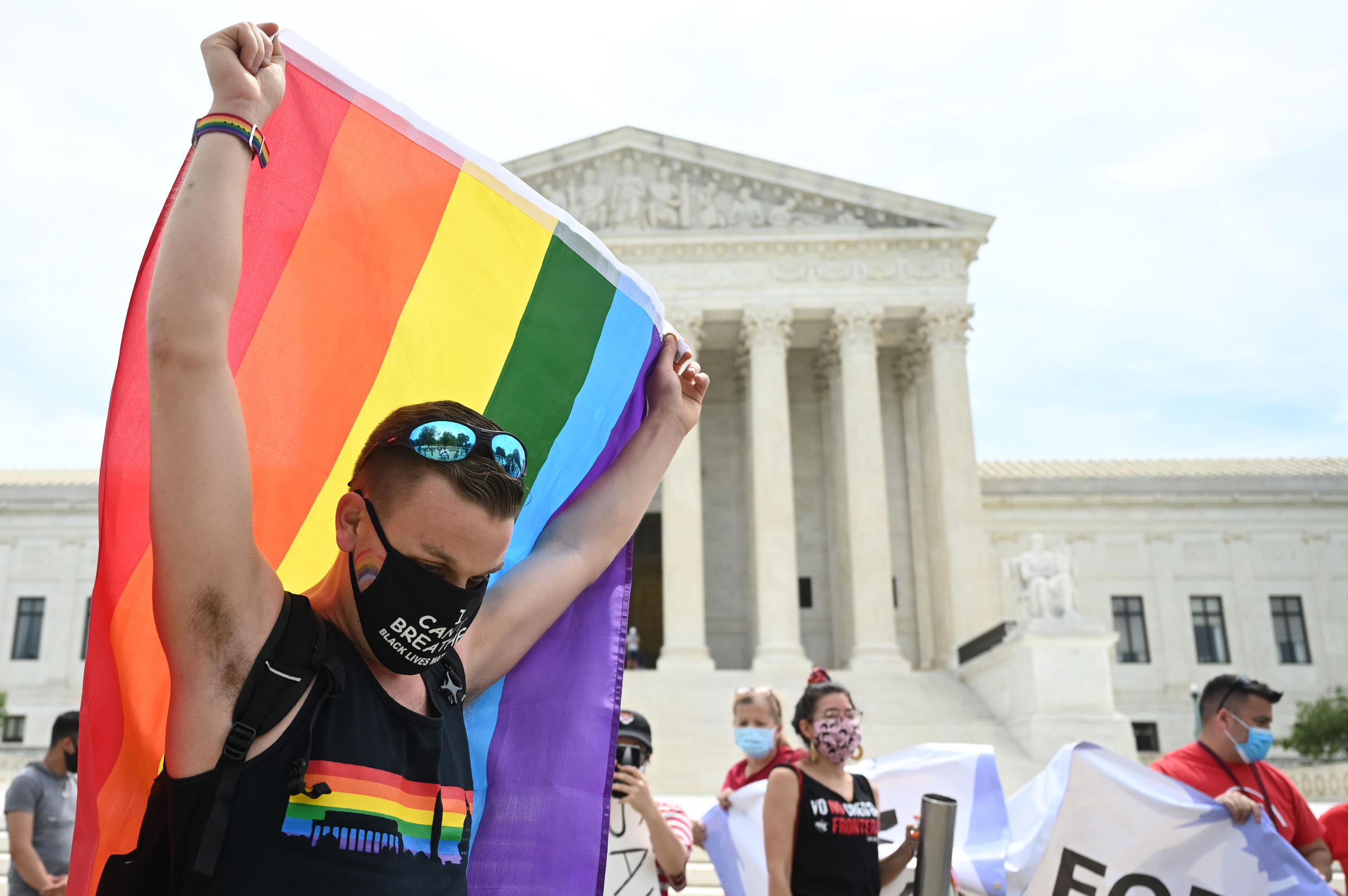 A person waves a rainbow flag in front of the US Supreme Court that released a decision saying federal law protects LGBTQ workers from discrimination