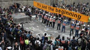 Des ouvriers démantèlent des barricades face à des militants prodémocratie et à des journalistes, le 11 décembre 2014 à Hong Kong.