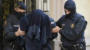 Photo de la police espagnole procédant à l'arrestation de jihadistes présumés à Barcelone, le 25 avril 2017.