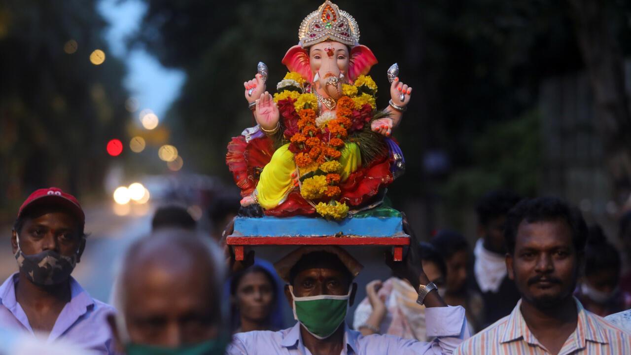 Un grupo de personas, algunas con máscaras protectoras, cargan una imagen de Ganesha, deidad de la abundancia, para mojarla en el mar arábigo como parte del festival Chaturthi Ganesha en Mumbai, India, el 23 de agosto de 2020.