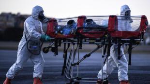 Bomberos de Minas Gerais con equipo de protección llevan una camilla de aislamiento para transportar pacientes infectados con coronavirus, el 22 de julio de 2020 en el aeropuerto de Pampulha, Belo Horizonte, Brasil