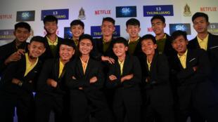 Integrantes del equipo de fútbol 'Jabalíes salvajes' junto con el entrenados Ekkapol Chantawong posan en una conferencia de prensa sobre producción de Netflix que narrará su historia. Bangkok, Tailandia. 30 de abril de 2019.