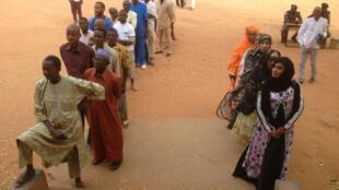 Des électeurs attendent devant un bureau de vote de Niamey lors du 1er tour de la présidentielle, le 21 février 2016.