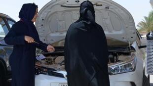Una entrenadora saudí muestra a una aprendiz cómo comprobar el nivel de aceite de un coche en la Escuela de Conducción Saudí (SDS), en la capital, Riad, el 24 de junio de 2019.