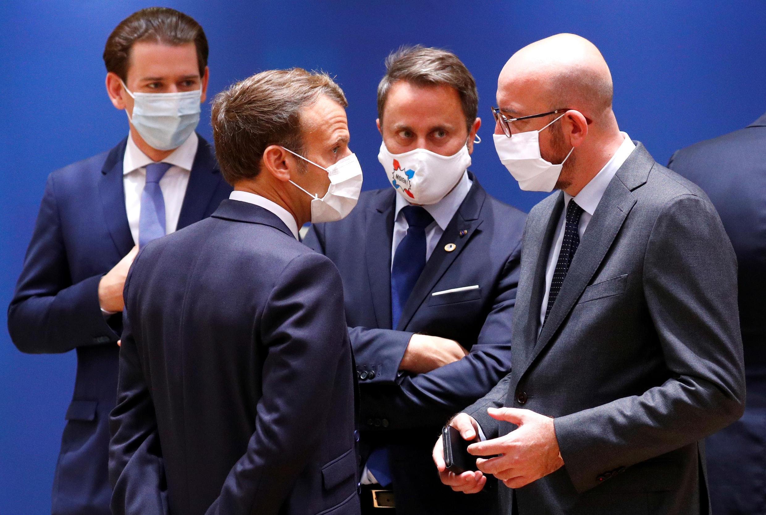 France's President Emmanuel Macron (L), Luxembourg's Prime Minister Xavier Bettel (C) and European Council President Charles Michel (R) speak as Austria's Chancellor Sebastian Kurz looks on during the second day of an EU summit in Brussels, Belgium on July 18, 2020.