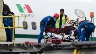 نقل إحدى المصابات المكسيكيات بعد وصول طائرتهن إلى مكسيكو في 18 أيلول/سبتمبر 2015