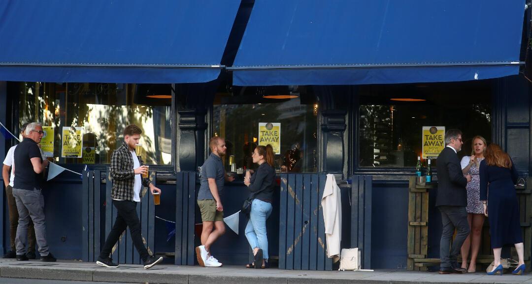 Gente bebe cerveza en un pub donde venden bebidas para llevar en Londres, Reino Unido, el 18 de junio de 2020.