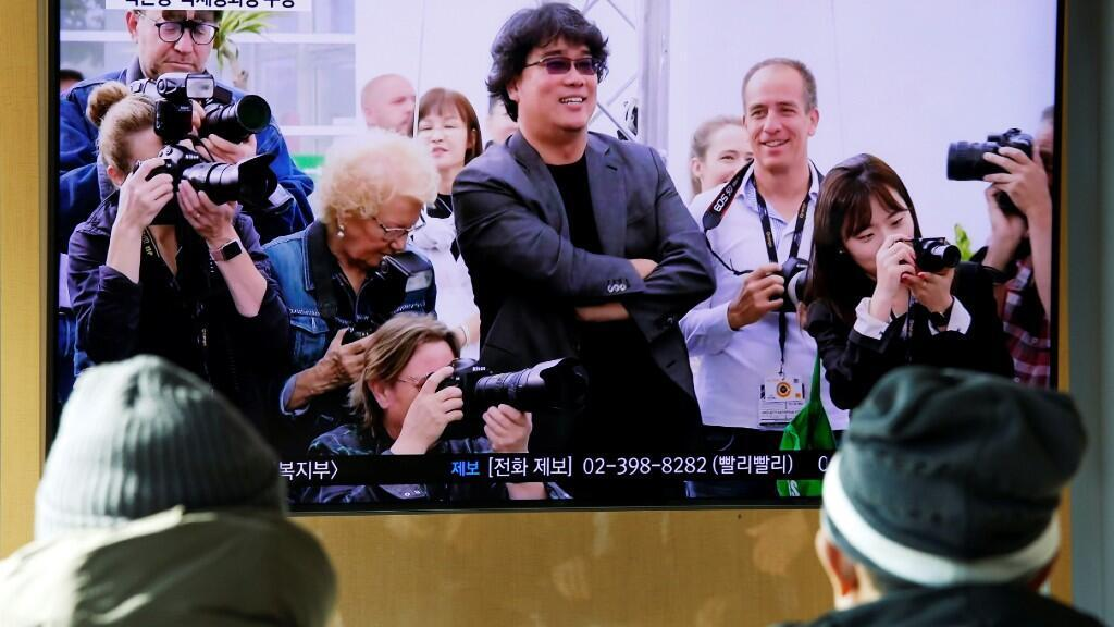 Ciudadanos surcoreanos ven la gala de los Óscar por las pantallas en Seúl.