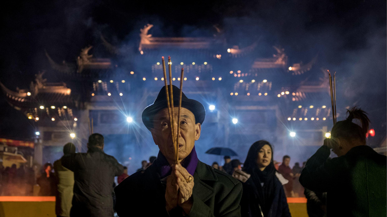 Un señor reza con varitas de incienso para celebrar el Año Nuevo Lunar, marcando el Año del Perro, en el templo de Longhua en Shanghai el 16 de febrero de 2018.