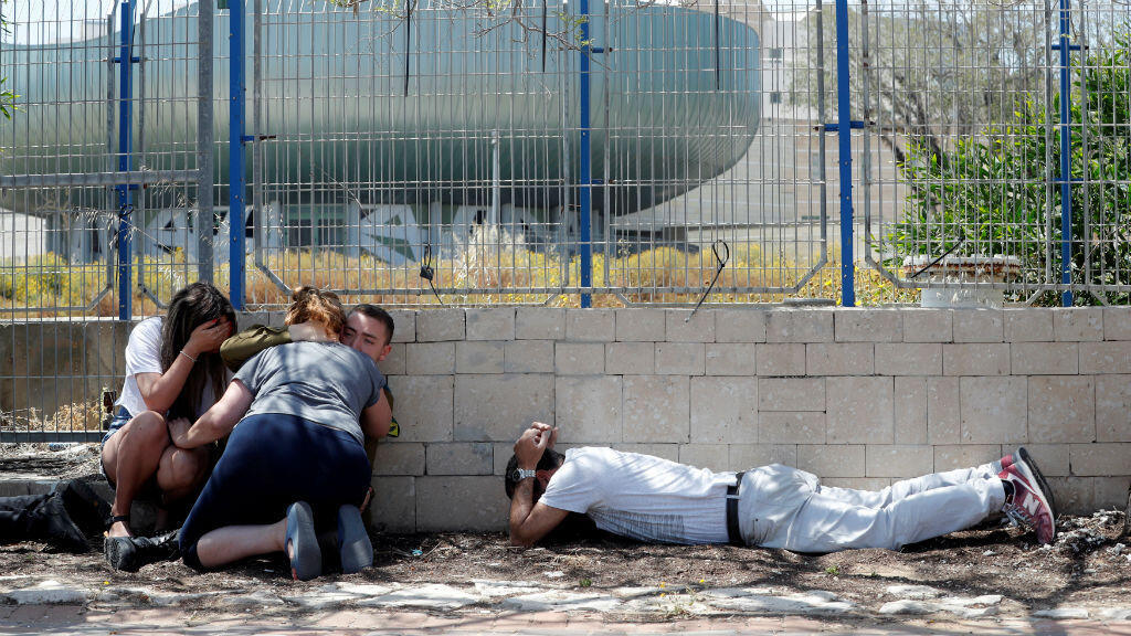 Los israelíes se esconden cuando escuchan las sirenas que advierten sobre los cohetes que llegan de Gaza, durante las hostilidades transfronterizas, en la ciudad de Ashkelon, en el sur de Israel, el 5 de mayo de 2019.