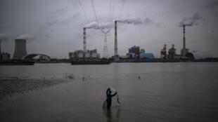 Un hombre pesca con red en el río Huangpu, frente a una central eléctrica de carbón, el 21 de febrero de 2017 en la ciudad china de Shanghái