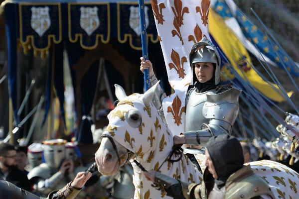 An actress plays Joan of Arc in full military gear at Sunday's ceremony.