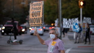 """A protester holds a sign reading """"Trump/Pence Out Now"""" during a demonstration against US President Donald Trump as votes continue to be counted following the 2020 US presidential election. at an intersection near downtown Atlanta, Georgia, November 6, 2020."""