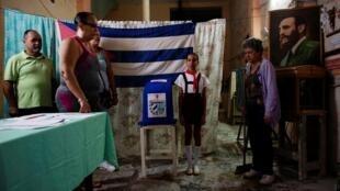Funcionarios electorales cantan el himno junto a la foto de Fidel Castro en La Habana, Cuba. 26 de noviembre de 2017