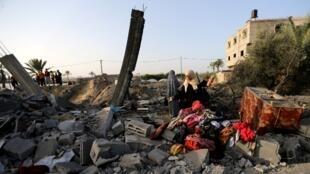 116/5000 Una mujer palestina inspecciona una casa destruida en un ataque aéreo israelí en el sur de la Franja de Gaza 13 de noviembre de 2019.