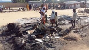 مدنيون يقفون وسط أثار هجوم نفذته بوكو حرام على مخيم للنازحين بنيجيريا