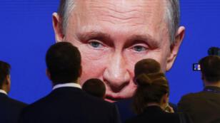 Los participantes del Foro Económico Internacional de San Petersburgo (SPIEF) se reúnen cerca de una pantalla electrónica que muestra al presidente ruso Vladímir Putin , quien habla durante una sesión del foro en San Petersburgo, Rusia, el 2 de junio de 2017.