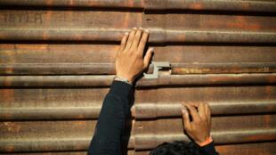 Un migrante, parte de una caravana de miles de personas que viajan desde América Central en ruta a los Estados Unidos, trata de mirar a los oficiales de la patrulla fronteriza de Estados Unidos a través de un agujero en el muro fronterizo entre los Estados Unidos y México en Tijuana, México, 25 de noviembre de 2018.