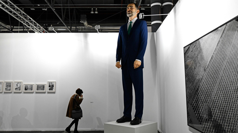 """Una mujer habla en su teléfono móvil junto a """"Ninot"""", una escultura gigante que representa al Rey Felipe VI de España, autoría de los artistas Santiago Sierra y Eugenio Merino, en ARCO Madrid, España, el 26 de febrero de 2019."""