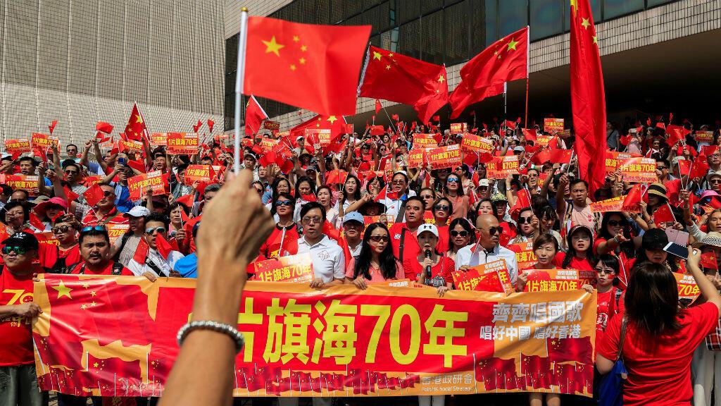 Los partidarios de China sostienen carteles y banderas nacionales durante un mitin en el Centro Cultural de Hong Kong, el 29 de septiembre de 2019.