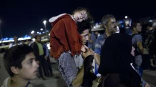 -عائلة سورية تنتظر حافلة النقل في مدينة بيري اليونانية